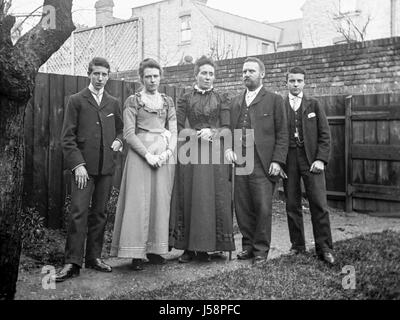 Full length portrait of an Edwardian family group of five adults standing together in the back garden of a house. - Stock Photo