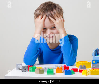 Little kid boy playing with colorful plastic construction bricks at home - Stock Photo