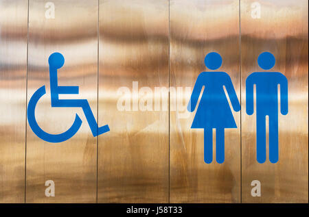 Sign outside toilet indicating facilities for the disabled, for women and for men. - Stock Photo