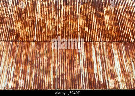 Rust patterns on weathered corrugated metal siding wall - Stock Photo