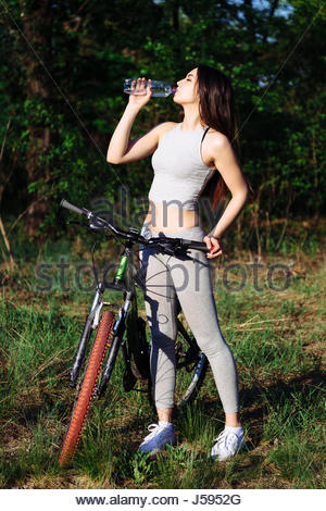 Young mixed race woman cyclist on mountain bike drinking water during cycling workout outdoor. Healthy lifestyle - Stock Photo