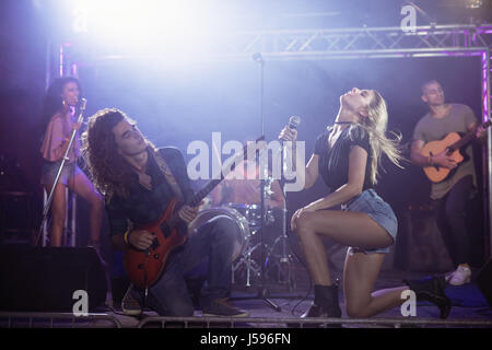 Female singer with male guitarist performing together on stage at nightclub - Stock Photo