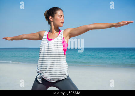 Young woman with eyes closed exercising at beach - Stock Photo