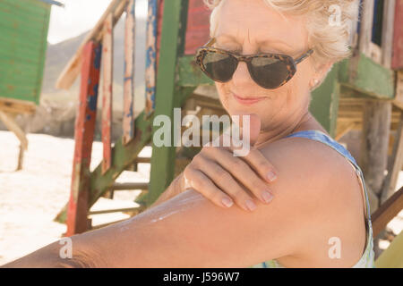Close up of woman applying suntan lotion while standing against hut at beach - Stock Photo