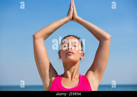Young woman with eyes closed against blue sky exercising at beach - Stock Photo