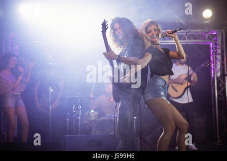 Female singer with male guitarist performing together at nightclub during music festival - Stock Photo