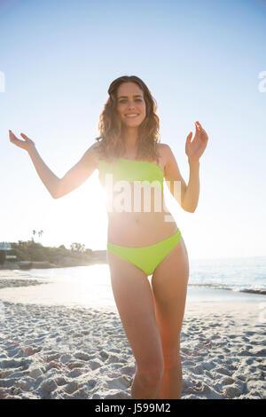 Portrait of young woman wearing bikini at beach on sunny day - Stock Photo