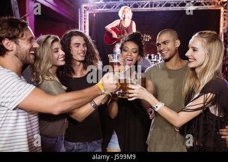 Smiling friends toasting beer glasses with performer singing in background at nightclub - Stock Photo