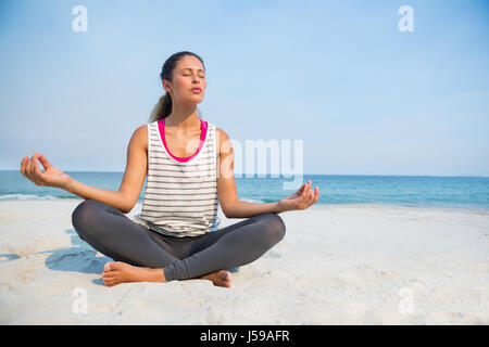 Full length of young woman with eyes closed meditating at beach against clear blue sky on sunny day - Stock Photo