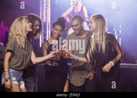 Happy friends toasting beer glasses with performer singing in background at nightclub - Stock Photo