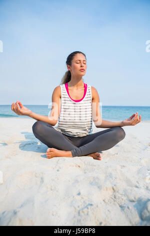 Full length of woman with eyes closed meditating at beach against clear blue sky on sunny day - Stock Photo