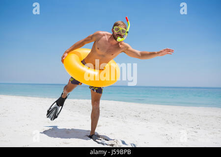 Man with snorkel wearing inflatable ring while standing at beach on sunny day - Stock Photo