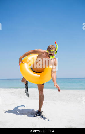 Playful man with snorkel wearing inflatable ring while standing at beach on sunny day - Stock Photo