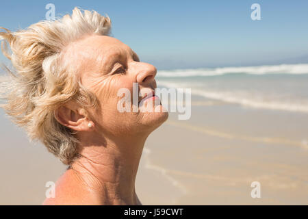 Close up of senior woman with eyes closed at beach - Stock Photo