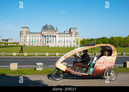 Tourist sightseeing rickshaw in front of the Reichstag in Berlin, Germany - Stock Photo