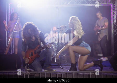 Young female singer with male guitarist performing together on stage at nightclub - Stock Photo