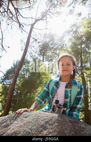 Portrait of girl leaning on the rock in the forest on a sunny day - Stock Photo