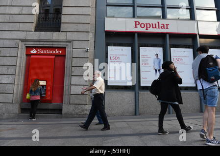 Madrid, Spain. 16th May, 2017. Several people walk past branches of Popular and Santander banks in Madrid, Spain. - Stock Photo
