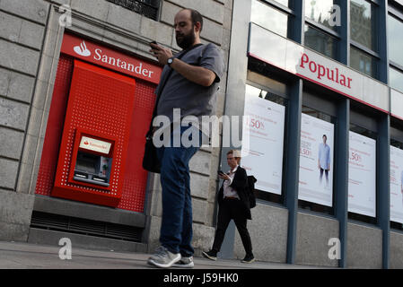 Madrid, Spain. 16th May, 2017. Two people walk past branches of Popular and Santander banks in Madrid, Spain Credit: - Stock Photo