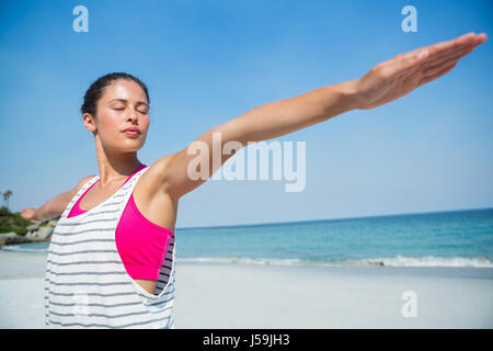 Woman with eyes closed exercising at beach - Stock Photo