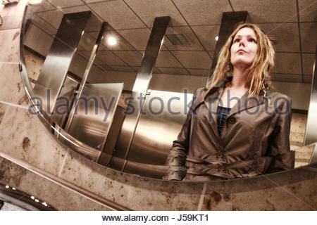 Woman looking at her reflection in the mirror in public washroom - Stock Photo