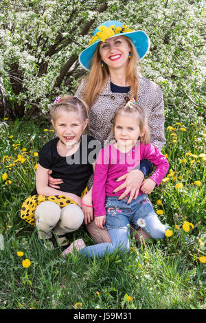 Portrait of a happy mother with two daughters in the spring among dandelions - Stock Photo