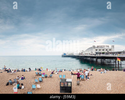 Holidaymakers on Brighton Beach and Pier - Stock Photo