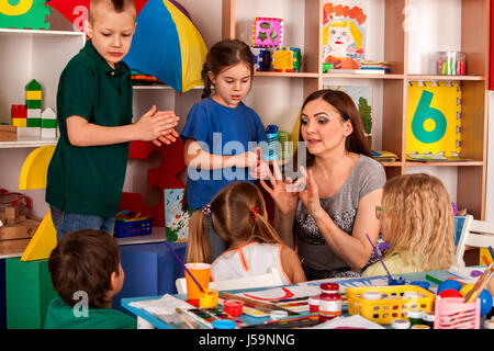 Small students girl finger painting in art school class. - Stock Photo
