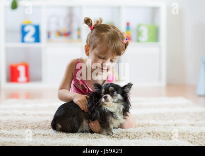 Lovely little girl and her pet dog - Stock Photo
