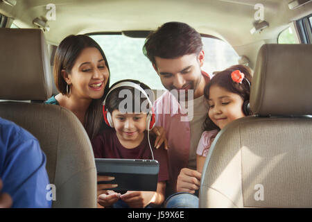Happy family sitting in back seat of car using digital tablet - Stock Photo