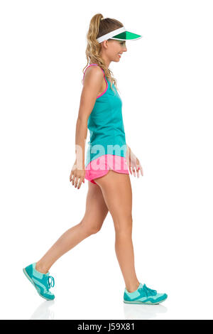 Smiling beautiful young woman in pink shorts green tank top and sneakers walking and looking away, Side view. Full - Stock Photo