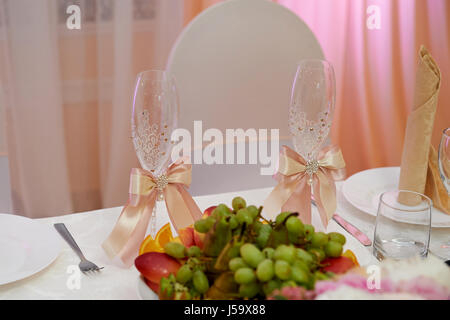 The Bridal table for the newlyweds on the wedding. Fruit and two glasses, decorated with satin ribbons, rhinestones - Stock Photo