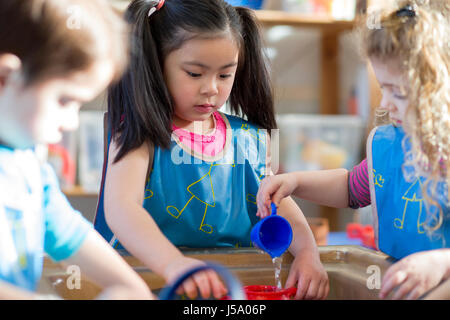 Young children wearing aprons are playing with a water table together in nursery. - Stock Photo