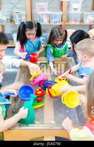 Group of nursery children playing at a water table with their teacher. - Stock Photo