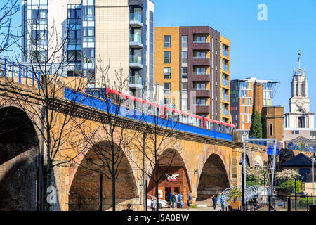 London, UK - April 8, 2017 - Limehouse viaduct with a Docklands Light Railway train passing by - Stock Photo