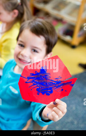 Little boy proudly holding up his painting to the camera. He has put blue paint on some red paper. - Stock Photo