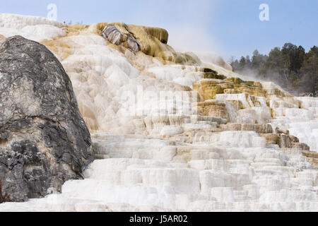 Mammoth Hot Springs with travertine terraces in foreground, the black Devil's Thumb on the left and steam rising - Stock Photo
