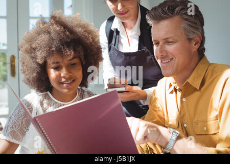 Couple placing order to waitress in restaurant - Stock Photo