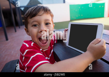 Portrait of cute boy holding digital tablet while sitting at table in school - Stock Photo