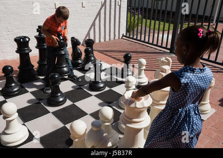 Classmates playing with large chess at school on sunny day - Stock Photo