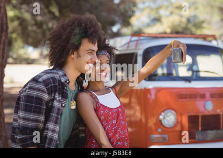 Happy woman with friend taking selfie while standing by van on field - Stock Photo