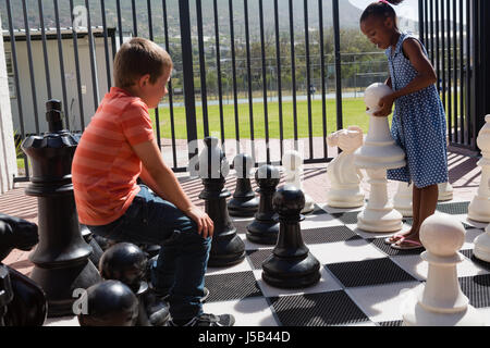 Classmates playing together with large chess at school on sunny day - Stock Photo