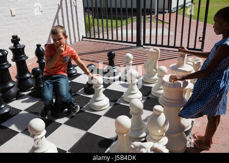 Boy and girl playing together large chess at school on sunny day - Stock Photo