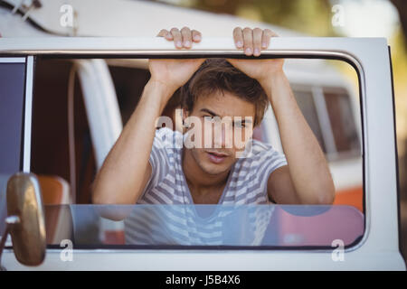 Portrait of serious young man leaning on van at forest - Stock Photo