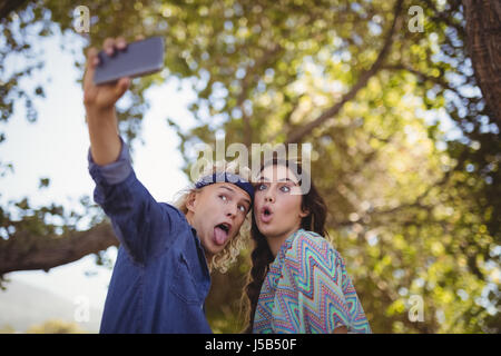 Happy couple making faces while taking selfie against trees at forest - Stock Photo