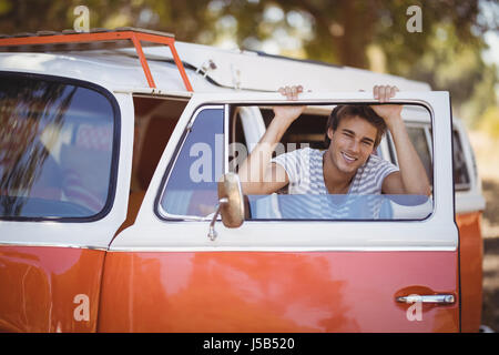 Portrait of cheerful young man leaning on van at forest - Stock Photo