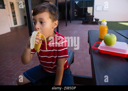 Boy looking away while eating banana at table in school - Stock Photo