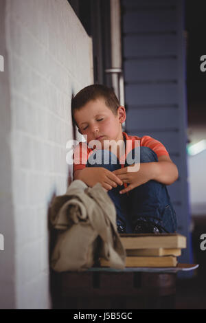 Boy sleeping while sitting on bench by wall in corridor at school - Stock Photo