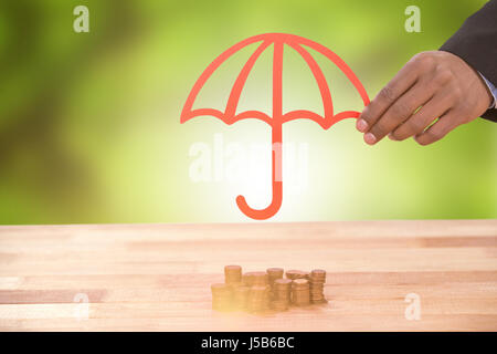 hand holding a red umbrella against trees in forest - Stock Photo