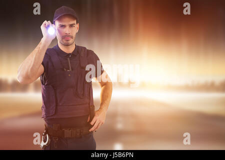 Portrait of security officer holding lit torch against city on the horizon - Stock Photo